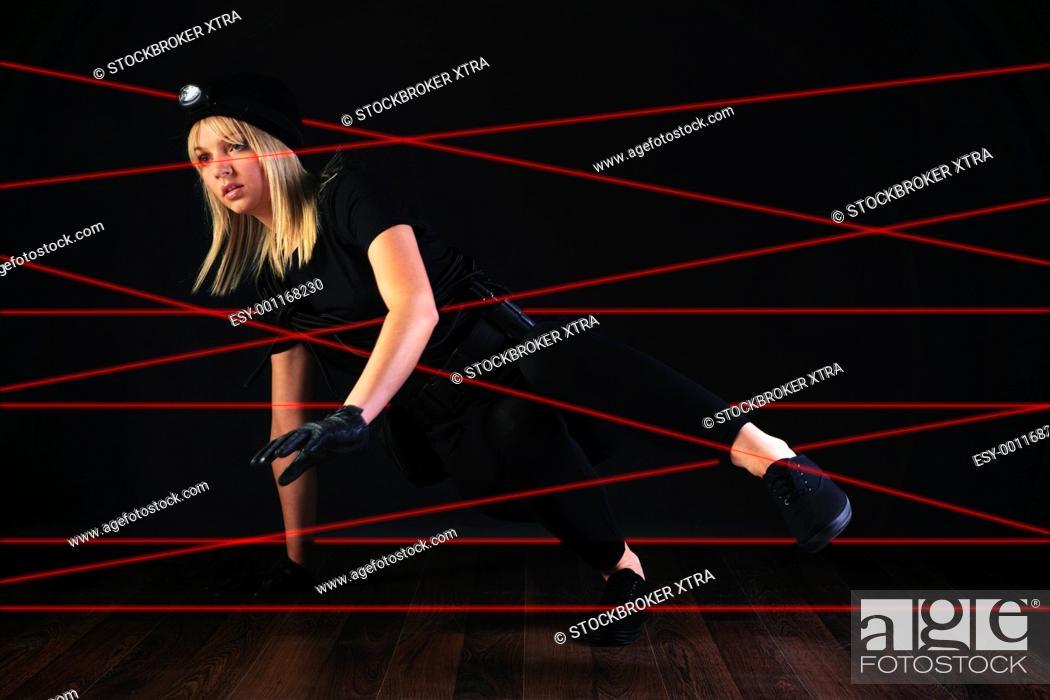 Cat burglar negotiating laser beam alarm system, Stock Photo
