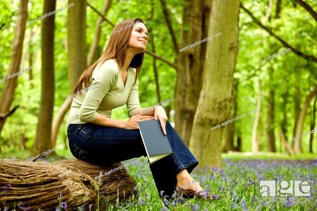 Stock Photo: A young woman sitting on a log, holding a book.