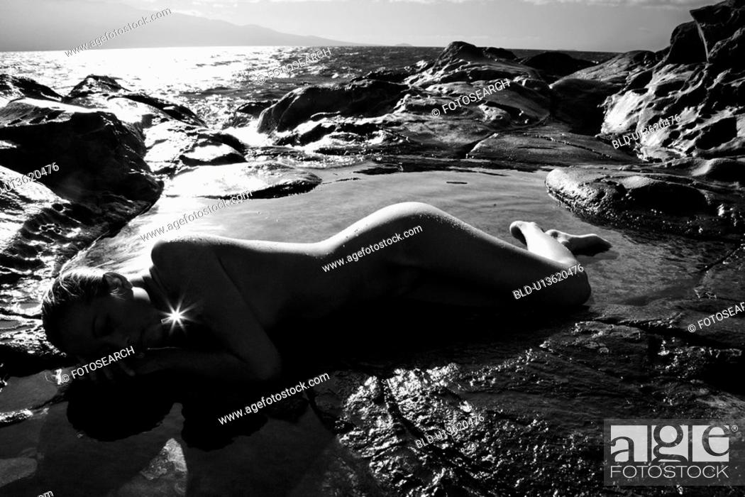 Stock Photo: Young nude woman lying on side in water on rocky beach.