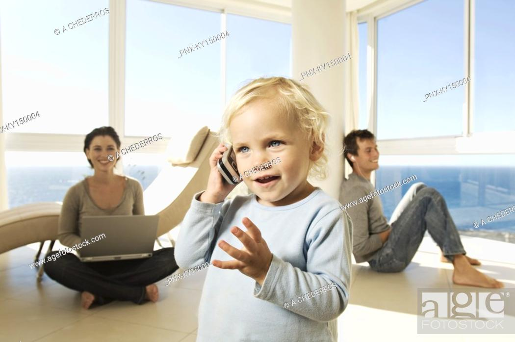 Stock Photo: Little girl using mobile phone, parents in background.