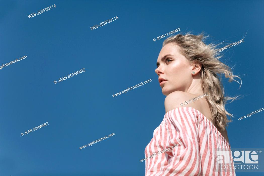 Stock Photo: Portrait of young woman under blue sky.