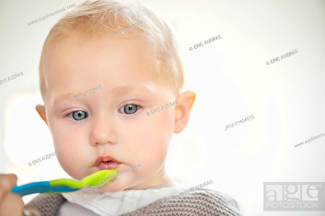 Stock Photo: Close-up of a baby girl holding a spoon.