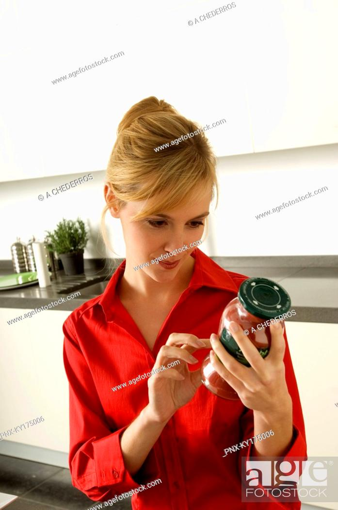 Stock Photo: Young woman reading a label on a jar.