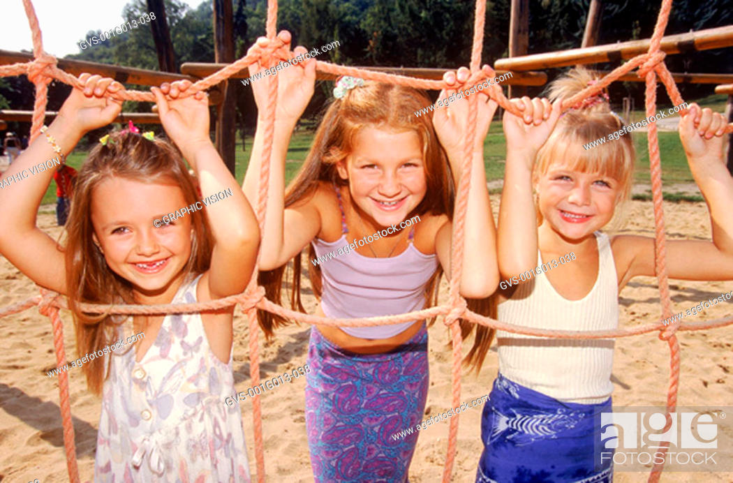 Stock Photo: Three young girls playing on a jungle gym.