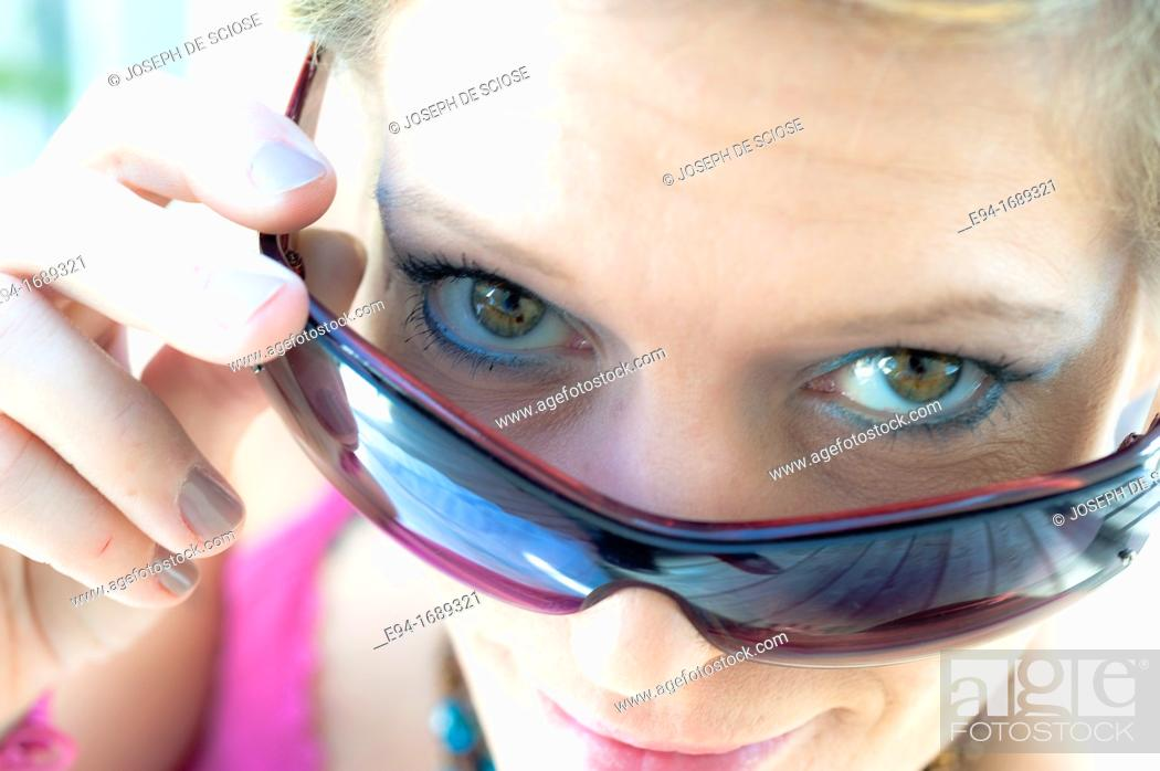 Stock Photo: 41 year old blond woman looking over her sun glasses.