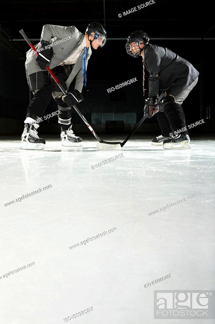 Stock Photo: Two businessmen playing ice hockey.