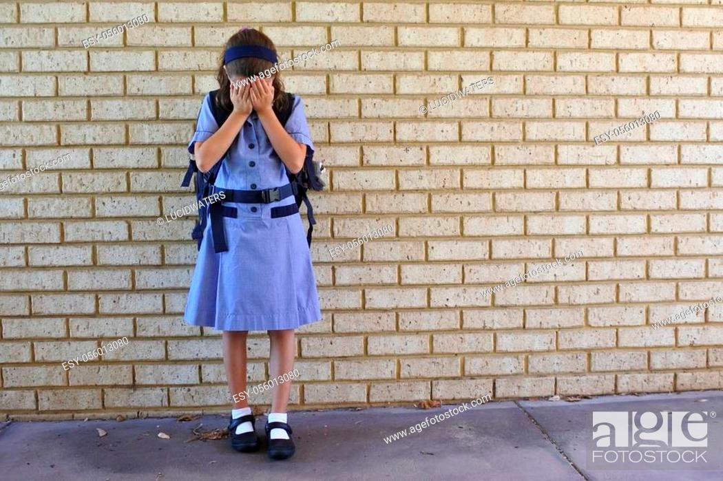 Imagen: Sad young schoolgirl (age 9-10) covering her face and crying in school yard. Child bullying concept. Real people. Copy space.
