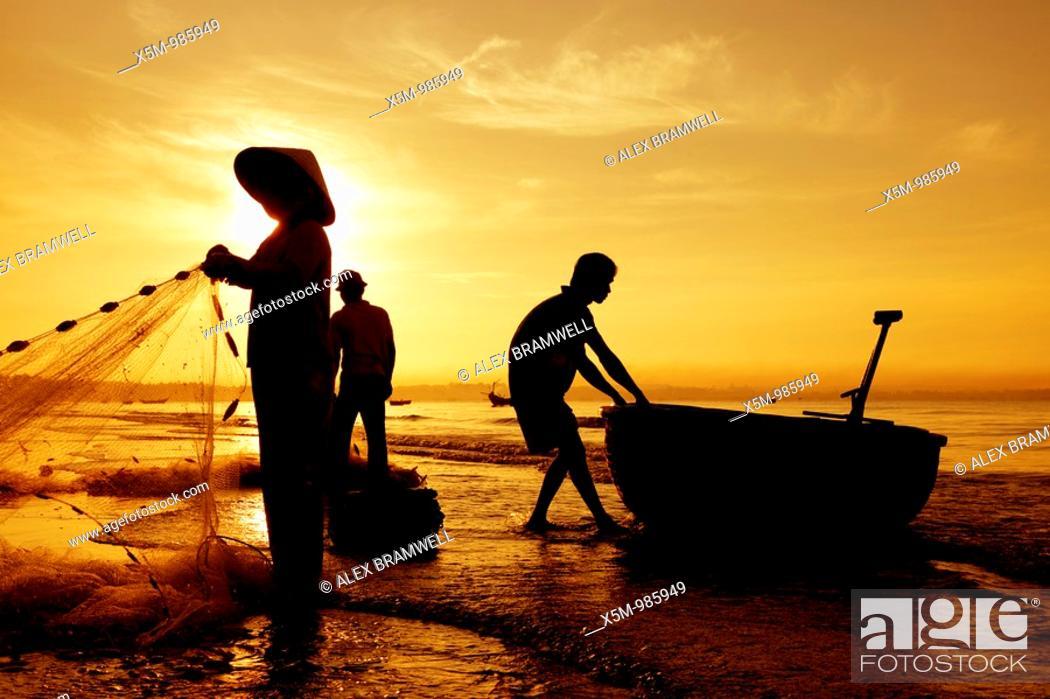 Stock Photo: Silhouetted fishermen on Mui Ne Beach in Vietnam.