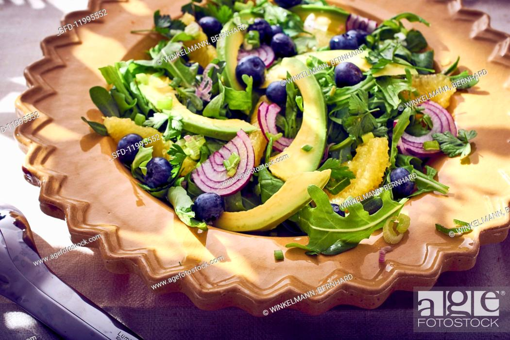 Stock Photo: Avocado salad with rocket, onion, blueberries and oranges.