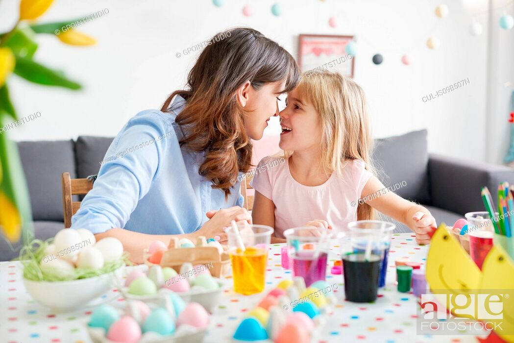Photo de stock: Woman and daughter nose to nose while painting easter eggs at table.