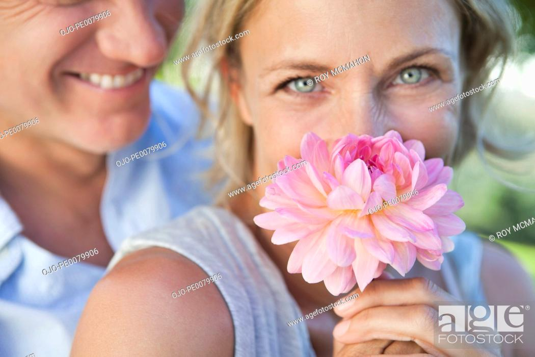 Stock Photo: Close up of woman smelling pink flower.