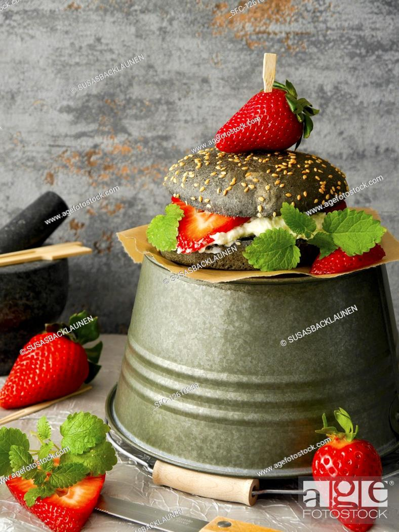 Stock Photo: A black burger with quark, strawberries and lemon balm.