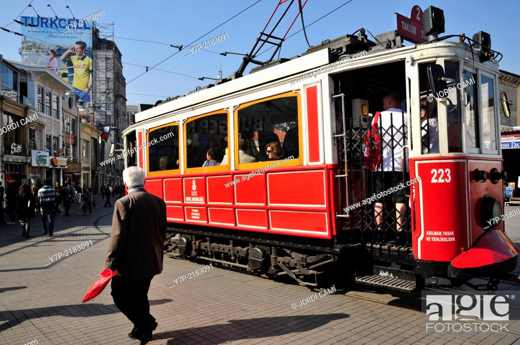 Stock Photo: The old tram in the confluence of Istiklal Cadessi and Taksim Square and Turkcell cellular phone operator publicity placard . Istanbul. Turkey.