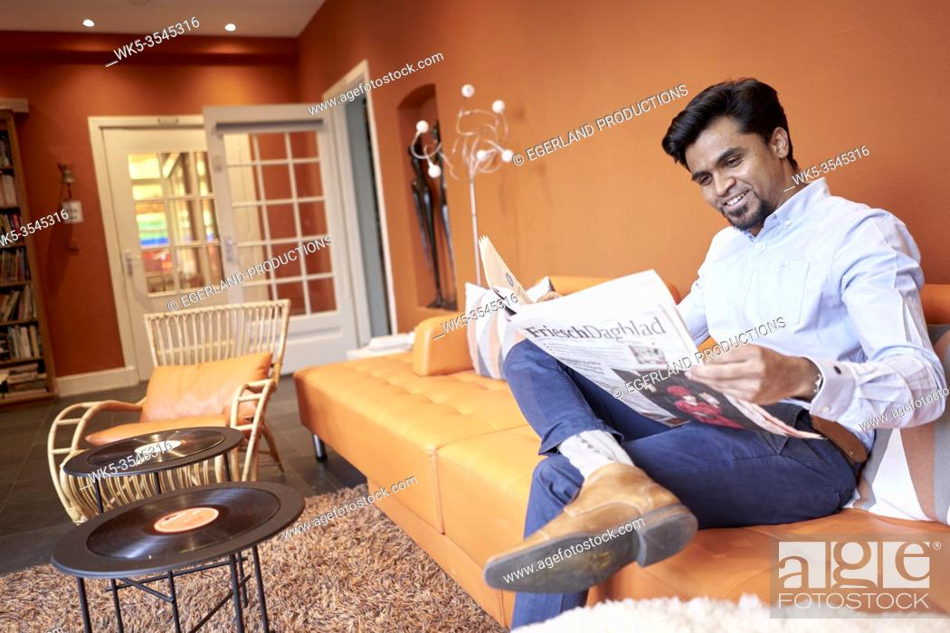 Stock Photo: Indian businessman reading newspaper in lobby.