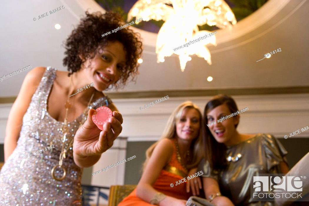 Stock Photo: Woman with gambling chips in casino, frinds in background, smiling, portrait, low angle view.