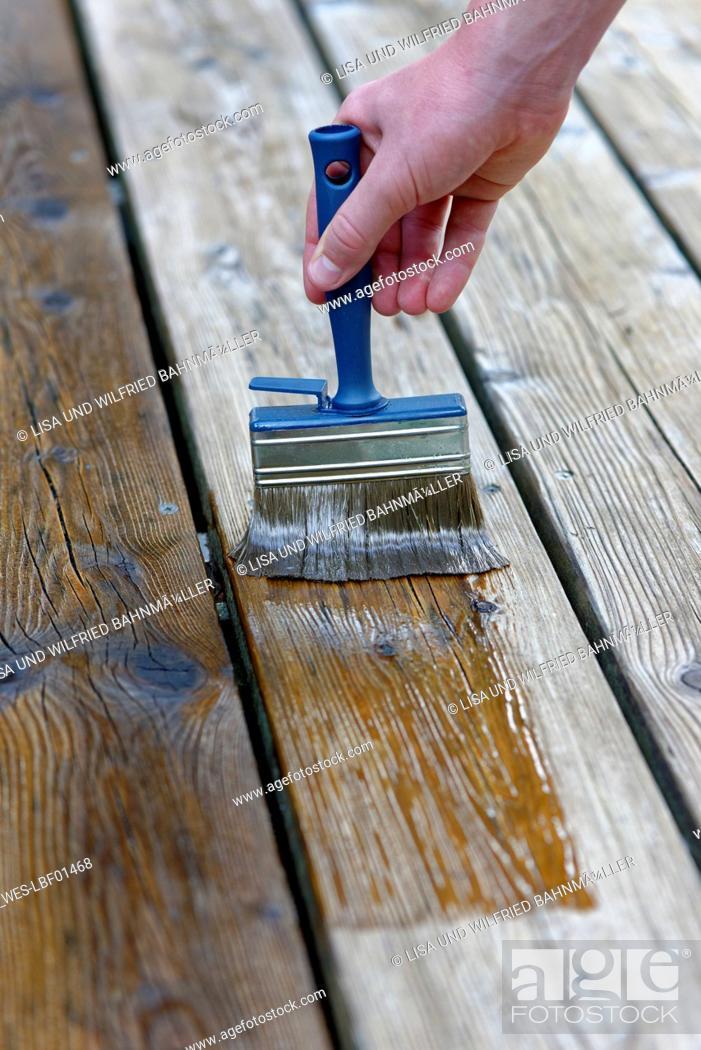 Stock Photo: Hand applying glaze on planks, close-up.