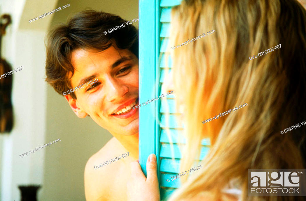 Stock Photo: Young man looking at a woman from behind a door.