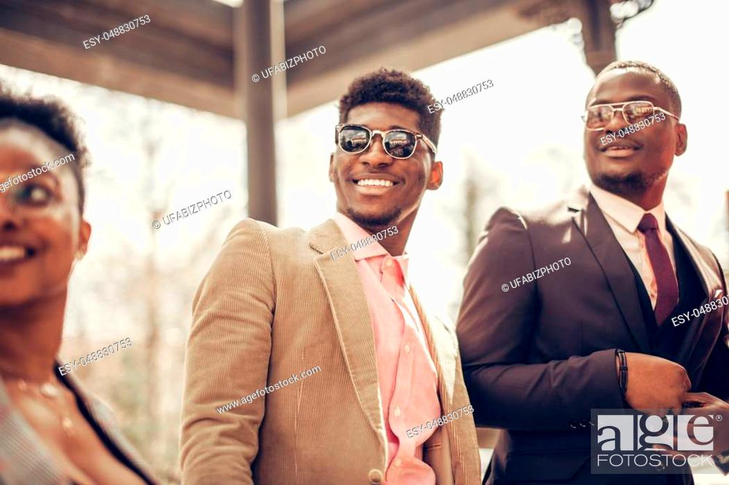 Stock Photo: low angle cropped view of african guys and woman with positive smiles watching the formal ceremony.