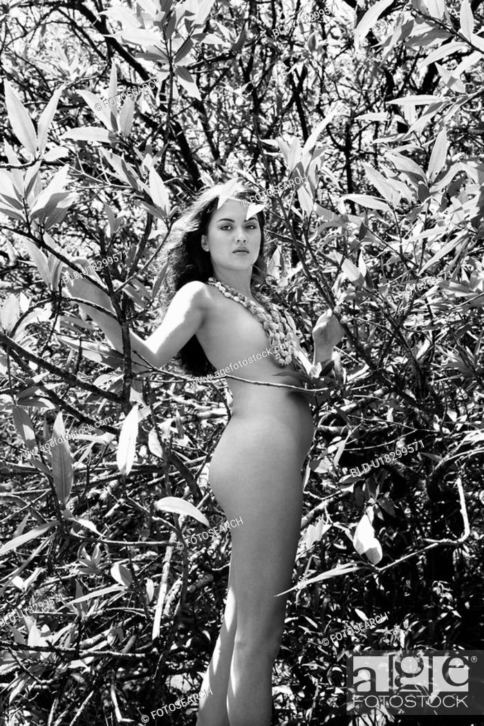 Stock Photo: Nude woman standing among branches and leaves.
