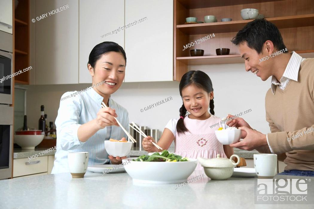 Stock Photo: Young couple and daughter eating a meal with chopsticks on kitchen counter.