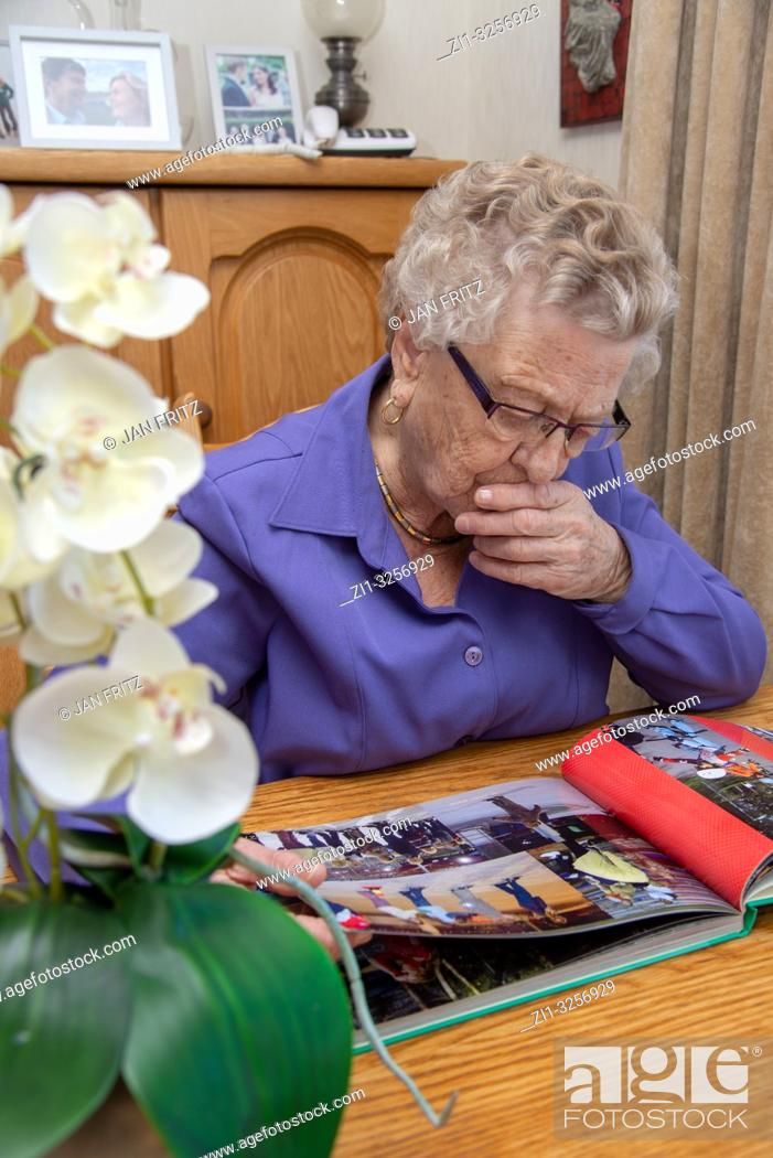 Photo de stock: old woman looking at photoalbum.