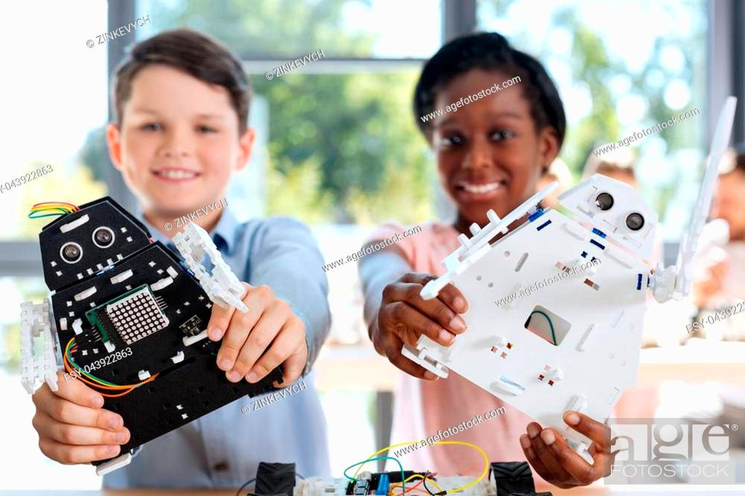 Stock Photo: Bright smiles. Happy pre-teen boy and girl standing in the robotics classroom and posing with their robot models, having created them by themselves.