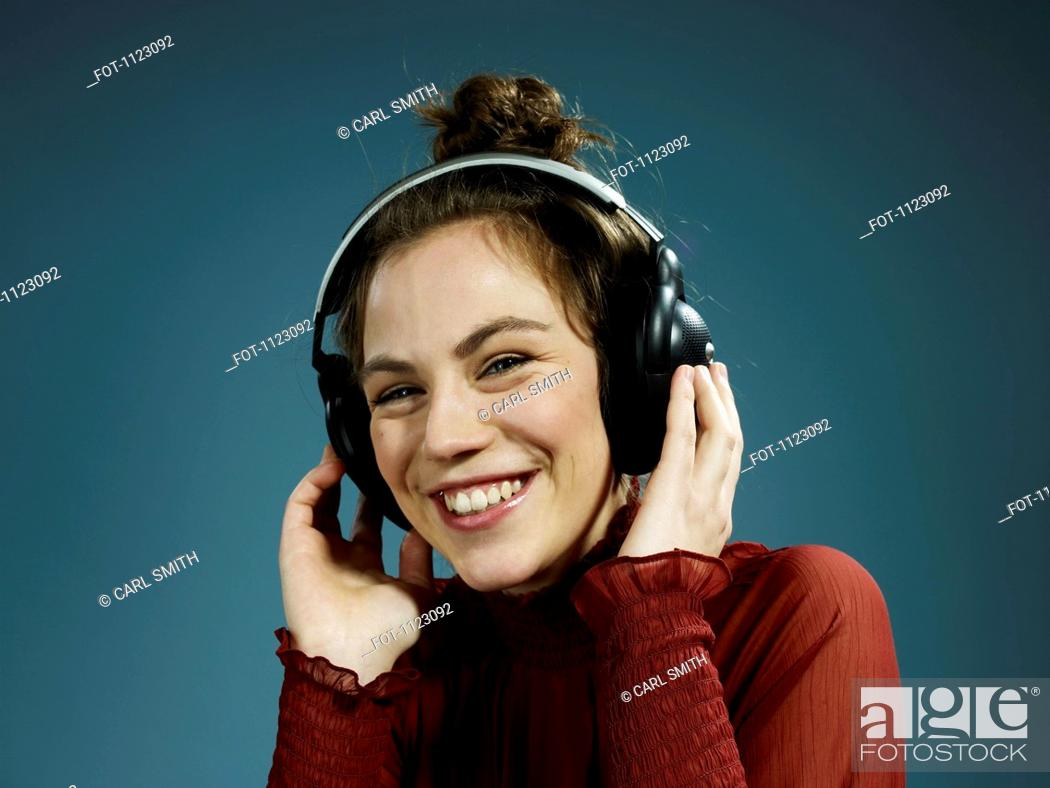 Stock Photo: A young hip woman wearing headphones and smiling.