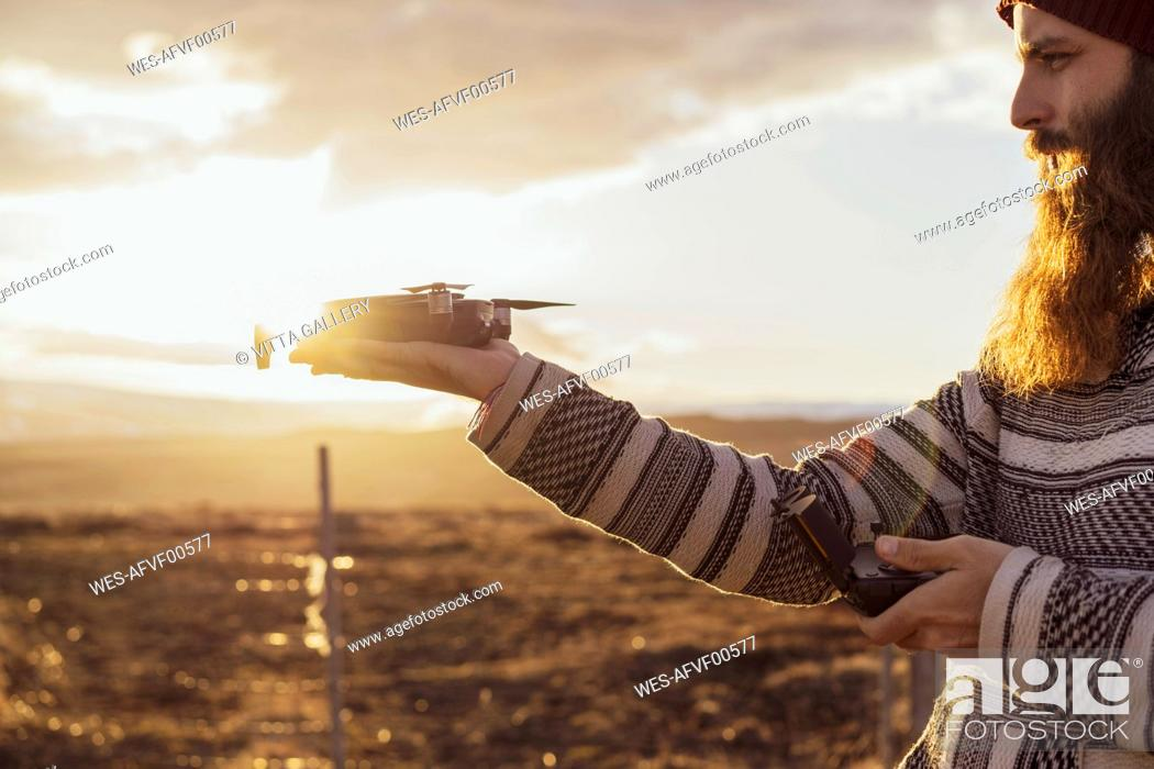 Stock Photo: Iceland, bearded man holding a drone at sunset.