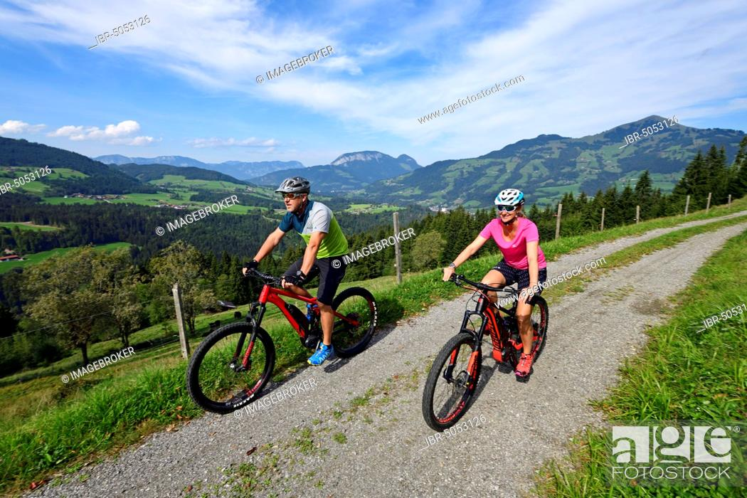 Stock Photo: Two cyclists with electric mountain bikes on the Glantersberg with view of the Hohe Salve, Kitzbühel Alps, Tyrol, Austria, Europe.