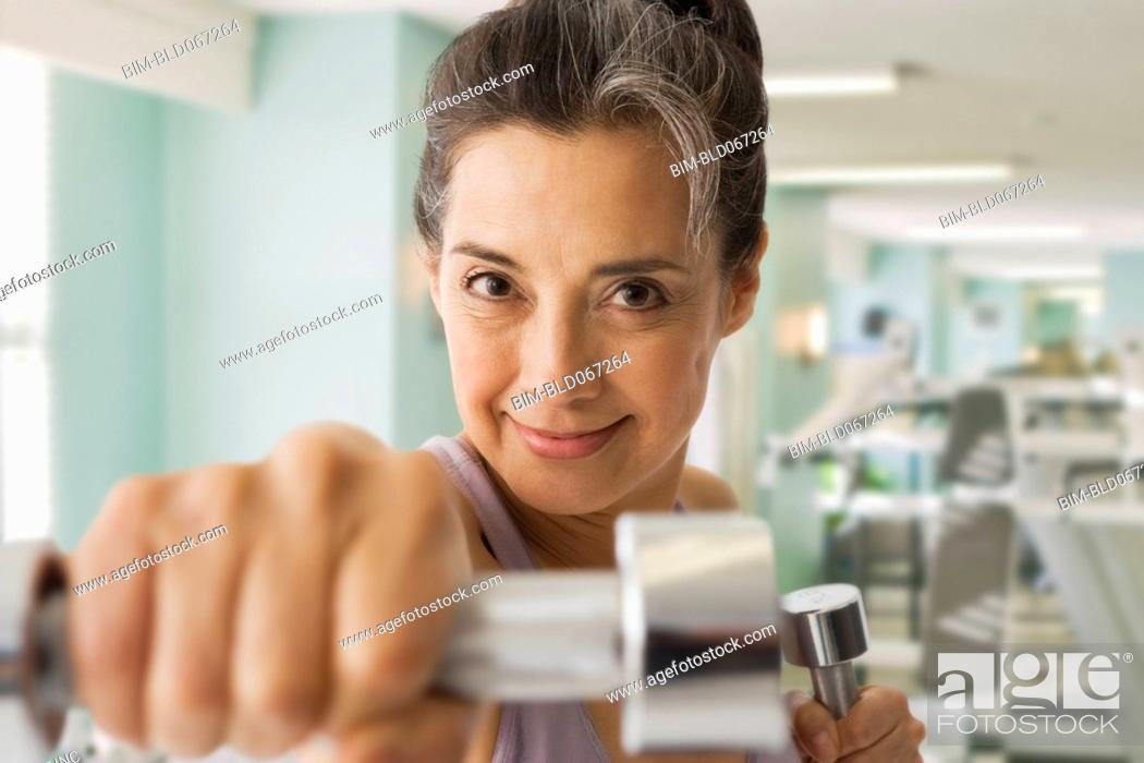 Stock Photo: Hispanic woman using hand weights in health club.