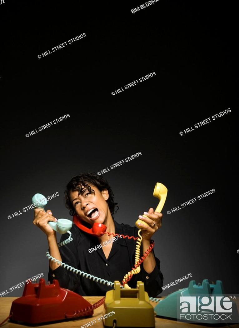 Stock Photo: Frustrated mixed race businesswoman holding old-fashioned telephones.
