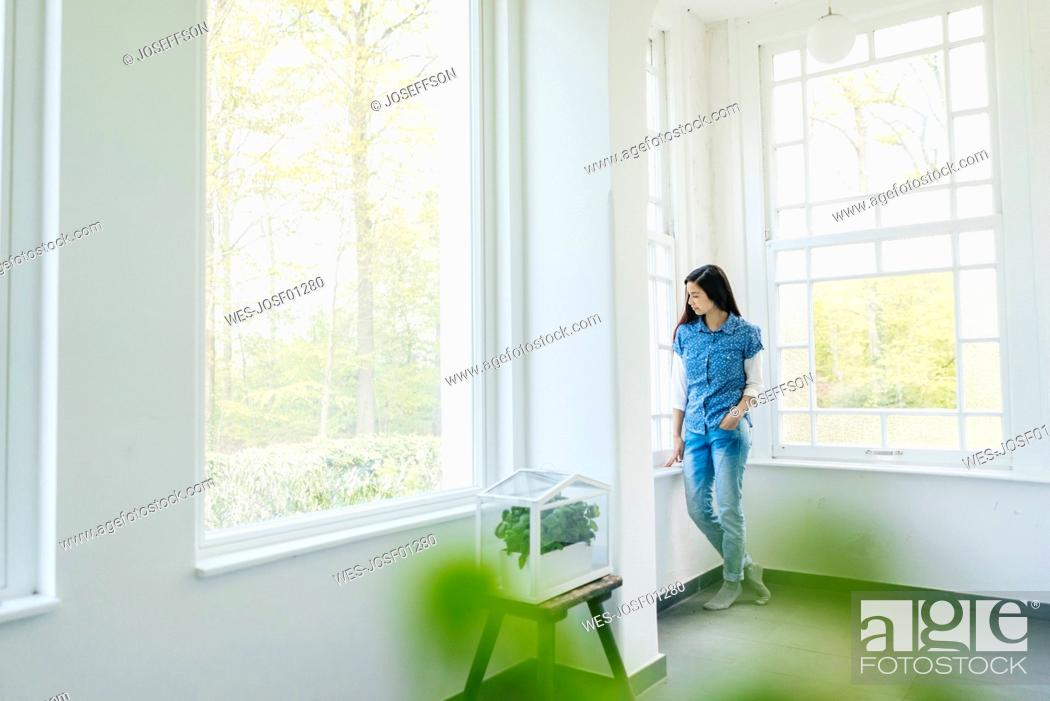 Stock Photo: Woman with herbs in glass box at the window.