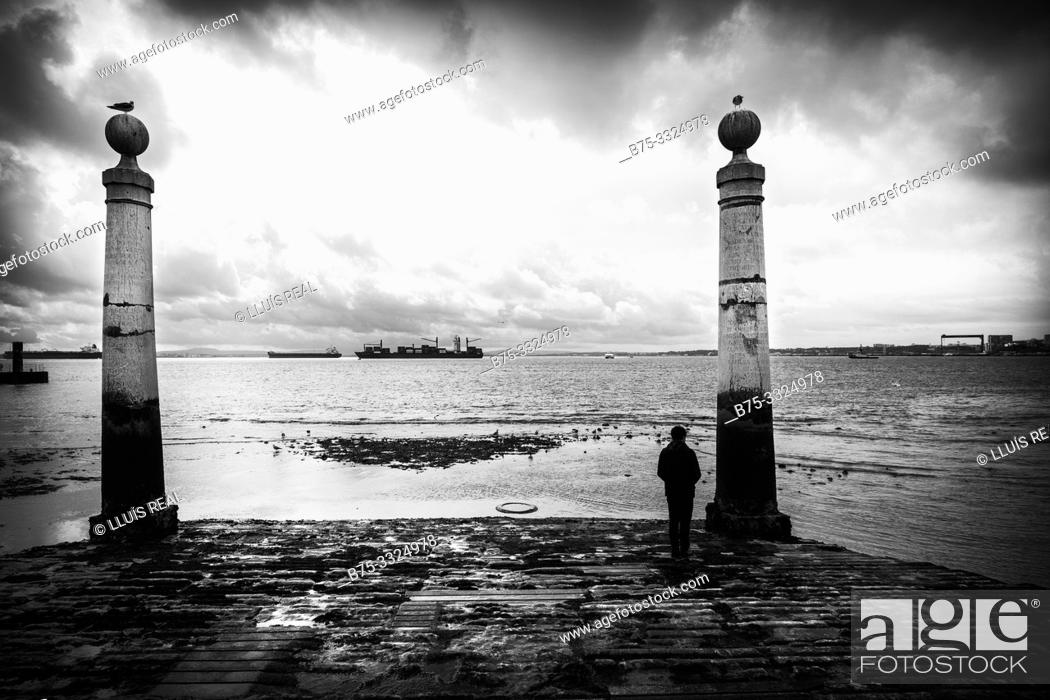 Stock Photo: A man looking at the sea Cais das Colunas, Plaza del Comercio, Lisbon, Europe.