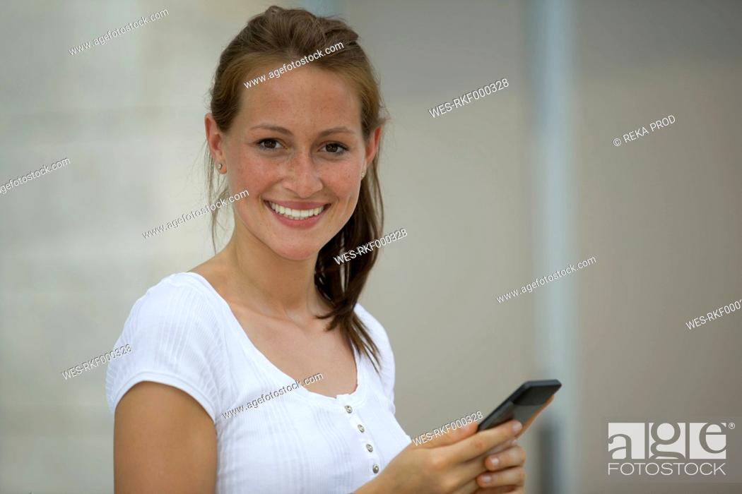 Stock Photo: Germany, North Rhine Westphalia, Cologne, Young woman using smart phone, smiling, portrait.