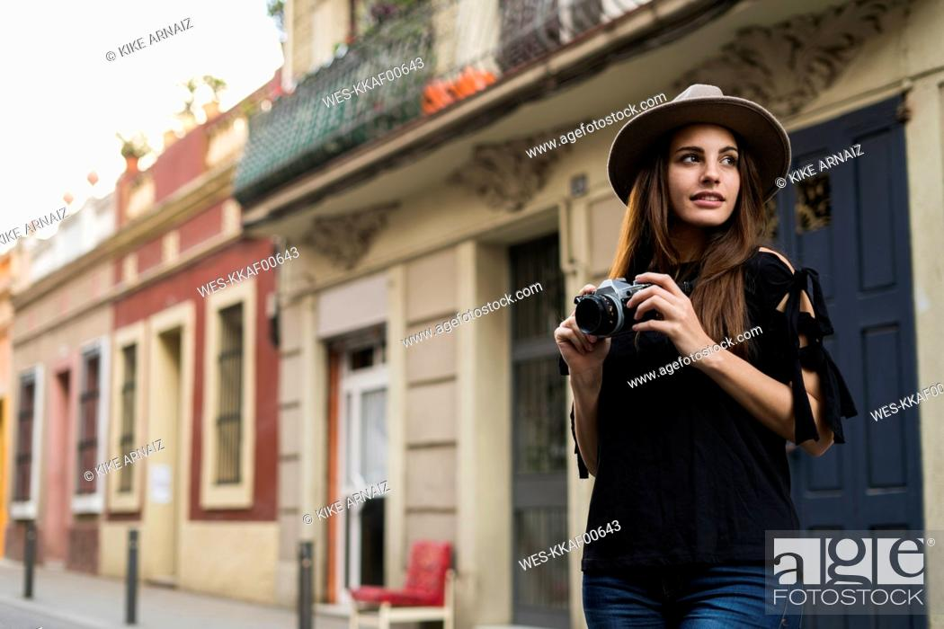Stock Photo: Portrait of smiling young woman with camera outdoors.
