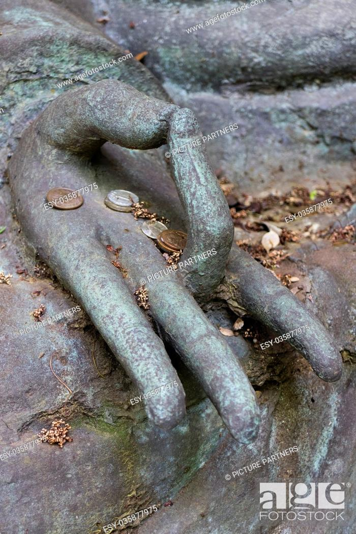 Photo de stock: Tokyo, Japan - Hand with some Japanese coins of a Buddha statue in the garden of the Nezu museum.