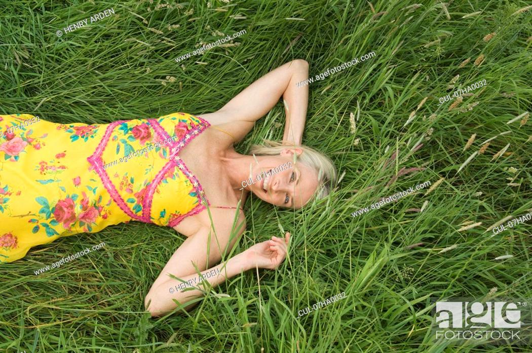 Stock Photo: Smiling woman lying in field.