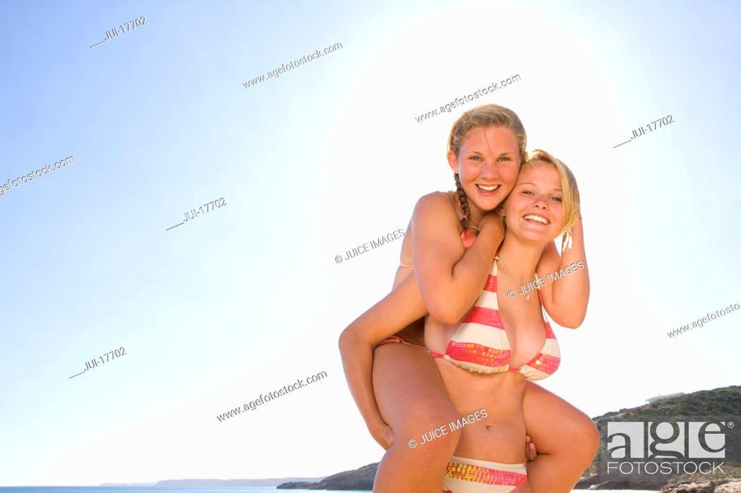 Stock Photo: Teenage girl carrying friend on shoulders.