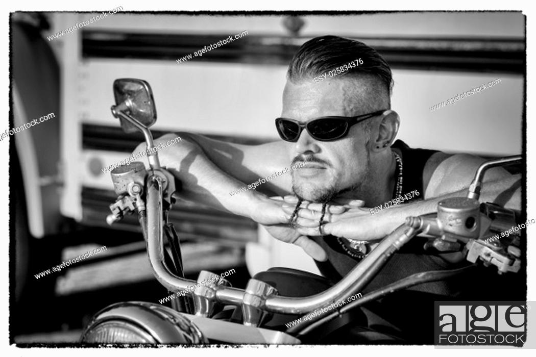 Stock Photo: Tough guy with sparrow beard, undercut, black rip shirt and sun glasses lolling on his chopper motorcycle in front of a yellow, American school bus..