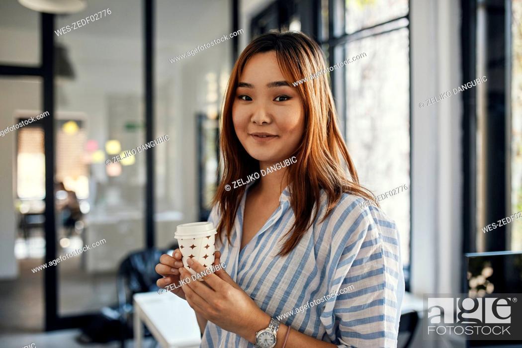 Stock Photo: Portrait of businesswoman having a coffee break in office.