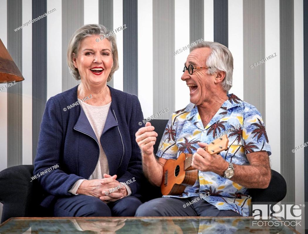 Imagen: Happy senior couple with man in Hawaiian shirt playing ukulele.