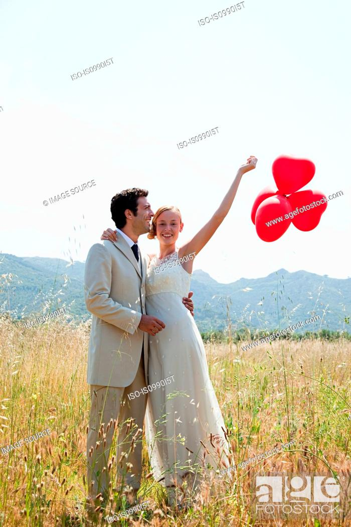 Stock Photo: Newlyweds in field with red heart shape balloons.
