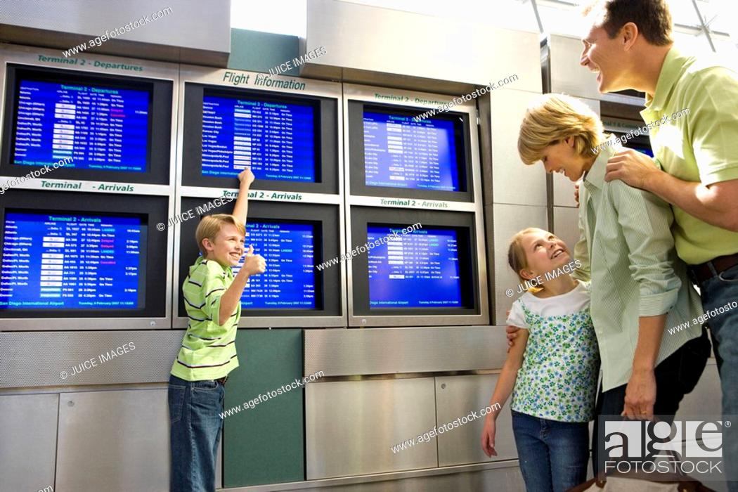 Stock Photo: Family standing in airport departure lounge, excited boy 8-10 pointing to flight information screen, father looking on, mother and daughter looking at one.