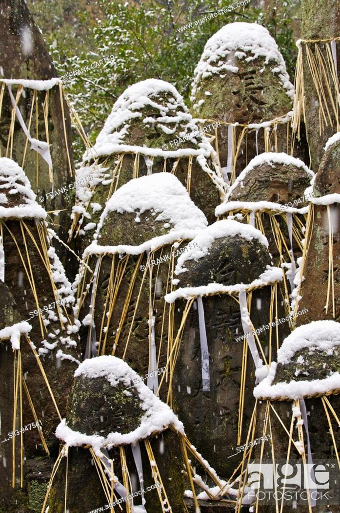 Stock Photo: Grave stones engraved with kanji characters, bound with straw rope and covered in snow at Fushi-inari-taisha shrine in Kyoto.