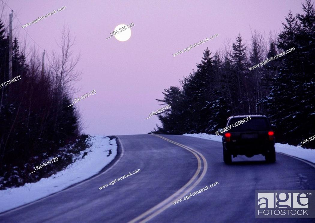 Stock Photo: vehicle on a highway at twilight with the moon rising in the winter.