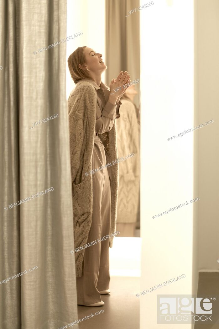 Stock Photo: happy fashionable woman with folded hands inside fitting room of clothing store, wearing new stylish one-piece jumpsuit combined with beige coat.
