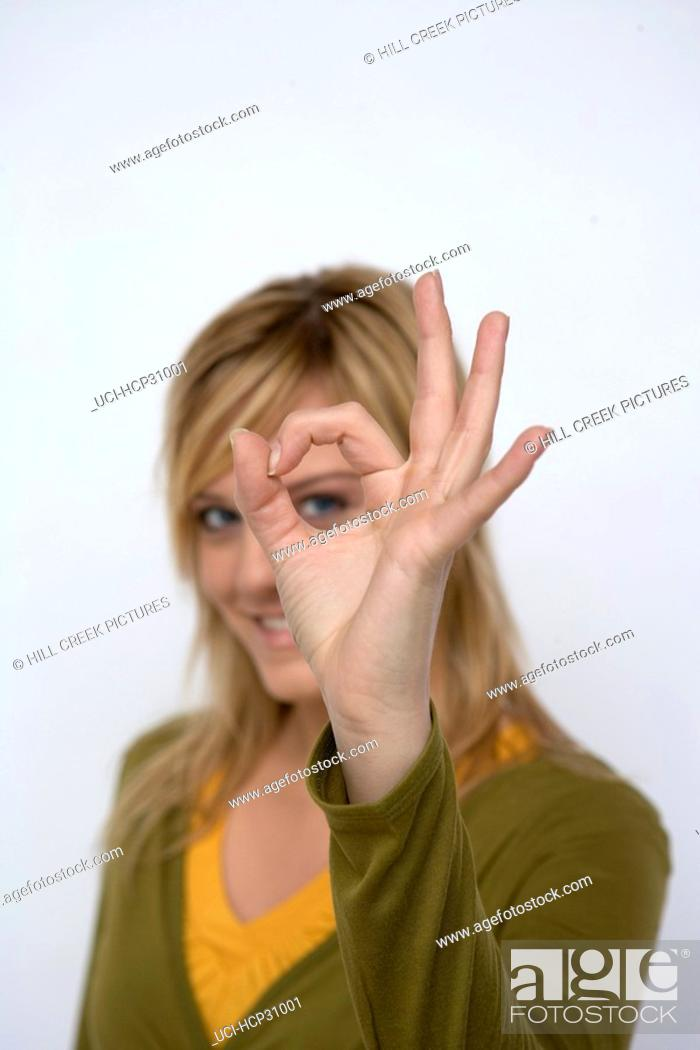 Stock Photo: Young woman looking through a hole in her fingers.