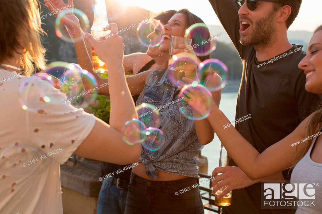 Stock Photo: Adult friends playing with floating bubbles at roof terrace party.