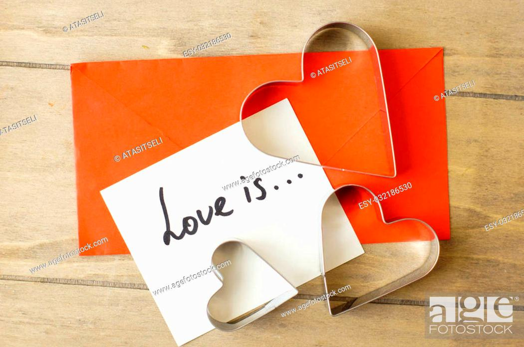 Stock Photo: Cookie cutter heart shape on the kitchen table with note.