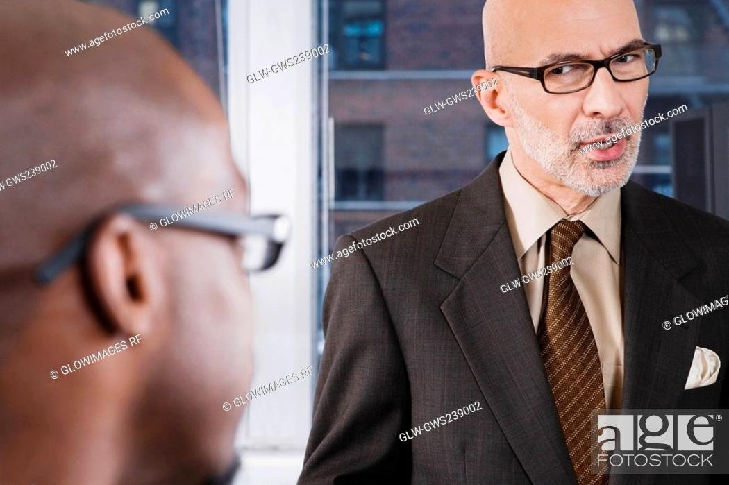 Stock Photo: Close-up of two businessmen discussing in an office.
